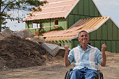Man with spinal cord injury in a wheelchair at his new accessible home under construction