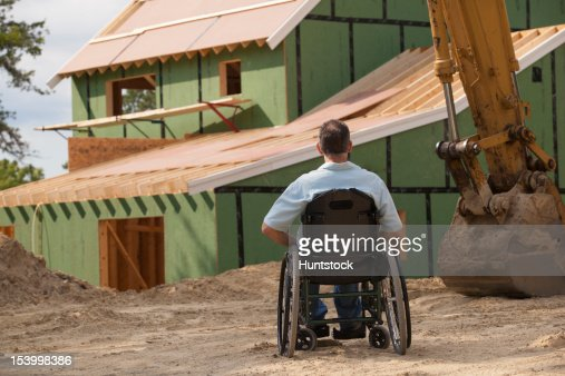 Man with spinal cord injury in a wheelchair at his new accessible home under construction : Stock Photo