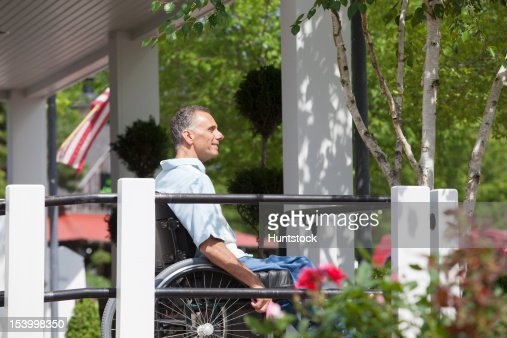 Man with spinal cord injury in a wheelchair at the top of an accessible ramp : Stock Photo