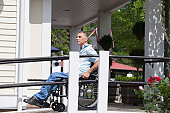 Man with spinal cord injury in a wheelchair at the top of an accessible ramp