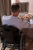 Man with spinal cord injury in a wheelchair brushing his teeth with toothpaste