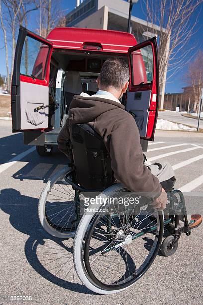 Man with spinal cord injury in a wheelchair closing automatic door of accessible van