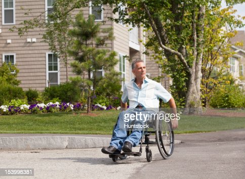 Man with spinal cord injury in a wheelchair crossing at accessible street entrance : Stock Photo