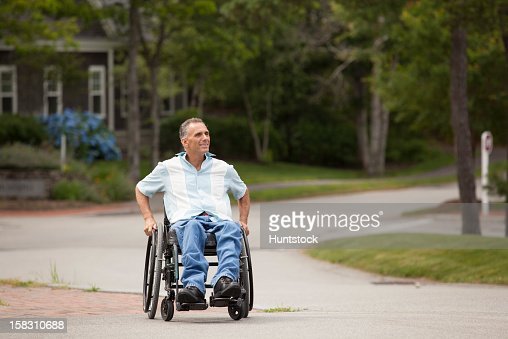 Man with spinal cord injury in a wheelchair crossing at accessible street walk : Stock Photo