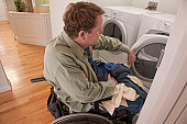 Man with spinal cord injury in a wheelchair doing his laundry at home