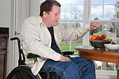 Man with spinal cord injury in a wheelchair eating fresh fruits at home