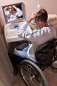 Man with spinal cord injury in a wheelchair fixing his hair