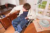 Man with spinal cord injury in a wheelchair getting dishes from cupboard to set the table