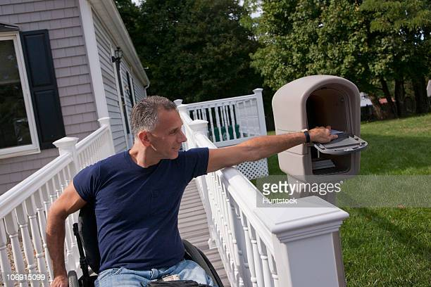 Man with spinal cord injury in a wheelchair getting his mail