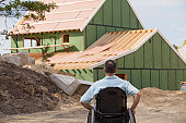 Man with spinal cord injury in a wheelchair looking at his new accessible home under construction