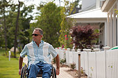Man with spinal cord injury in a wheelchair on a suburb walk with homes