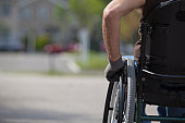 Man with spinal cord injury in a wheelchair on street corner