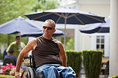 Man with spinal cord injury in a wheelchair sitting at a cafe