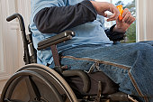 Man with spinal cord injury in a wheelchair taking pill from bottle with disabled hands