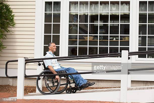 Man with spinal cord injury in a wheelchair using accessible ramp
