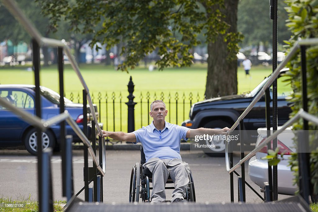 Man With Spinal Cord Injury In Wheelchair Approaching Outdoor Wheelchair  Ramp : Stock Photo