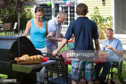 Man with spinal cord injury in wheelchair at family picnic : Stock-Foto
