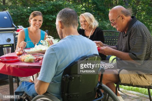 Man with spinal cord injury in wheelchair at family picnic with grandparents included : Stock Photo