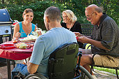 Man with spinal cord injury in wheelchair at family picnic with grandparents included