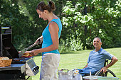 Man with spinal cord injury in wheelchair enjoying picnic with his wife