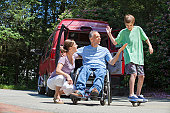 Man with spinal cord injury in wheelchair giving high-five to son on skateboard