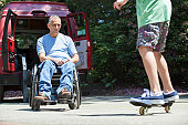 Man with spinal cord injury in wheelchair watching his son on skateboard
