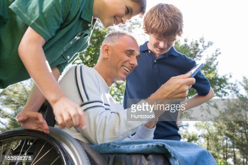 Man with spinal cord injury in wheelchair with his sons reading a tablet : Stock Photo
