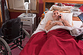 Man with spinal cord injury lying on the bed talking on a mobile phone