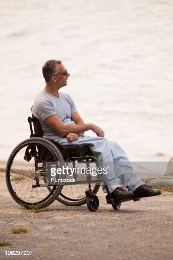 Man with spinal cord injury sitting in a wheelchair at seaside : Stock Photo