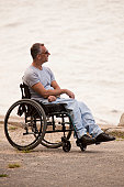 Man with spinal cord injury sitting in a wheelchair at seaside