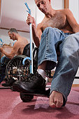 Man with spinal cord injury taking off his shoes with an extension tool