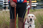 Man with spinal cord injury using a cane and standing with a service dog