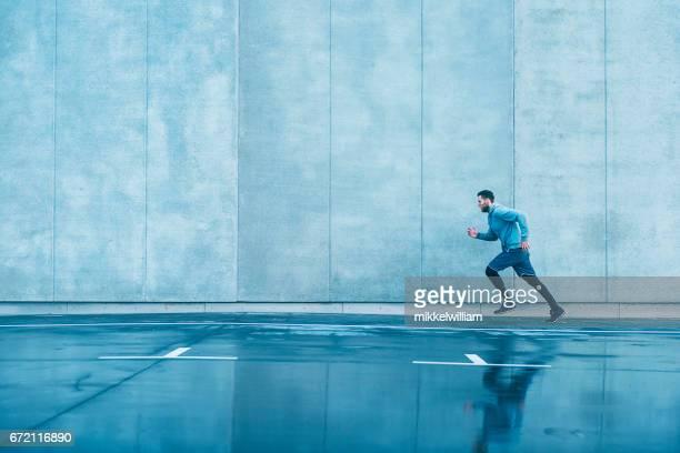 Mann mit Sportkleidung läuft schnell neben Betonwand
