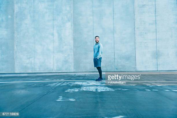 Man with sports clothes stands outside next to big concrete wall
