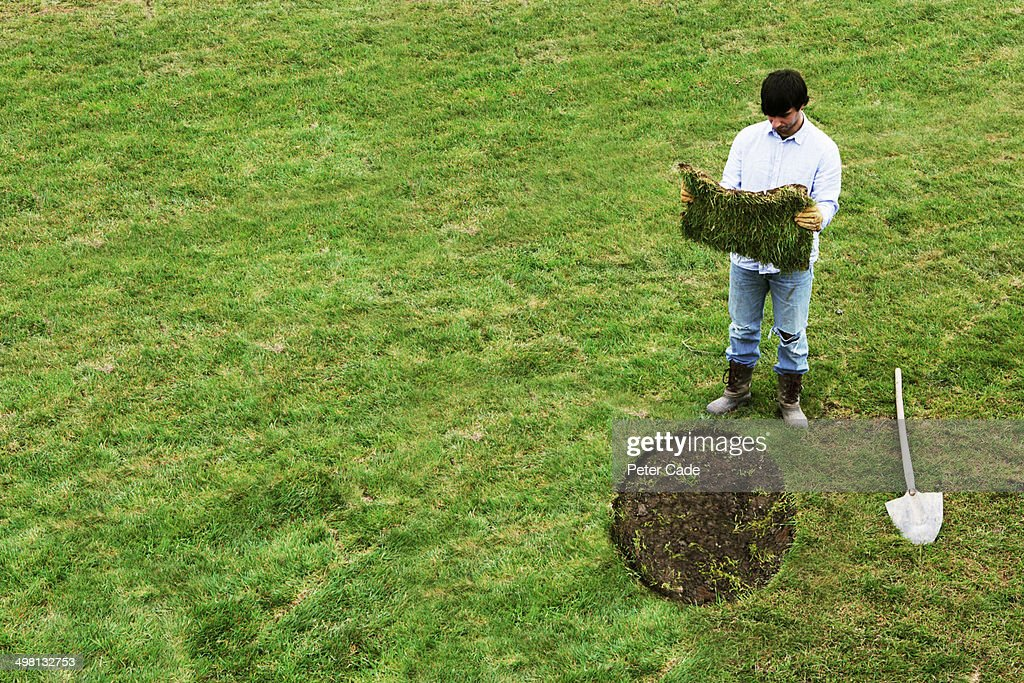 Man with square turf to lay in round gap on lawn