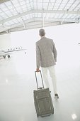 Man with suitcase walking out of airplane hanger