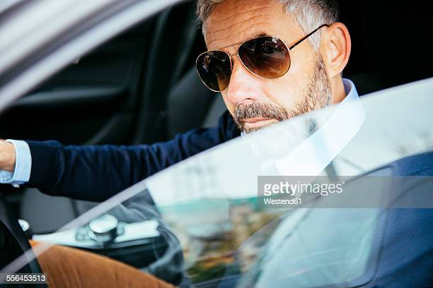 Man with sunglasses driving car