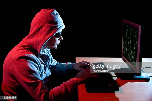 Man with sunglasses hacks computer at night
