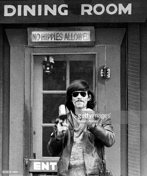 A man with sunglasses poses for a portrait in front of a dining room restaurant with a 'No Hippies Allowed' sign circa 1968 in San Francisco...