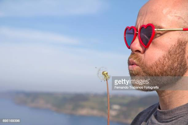 Man with sunglasses with heart shape blows dandelion flower