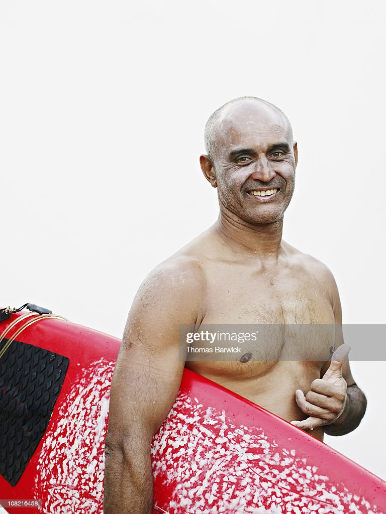 Man with sunscreen on face holding surfboard : Stock Photo