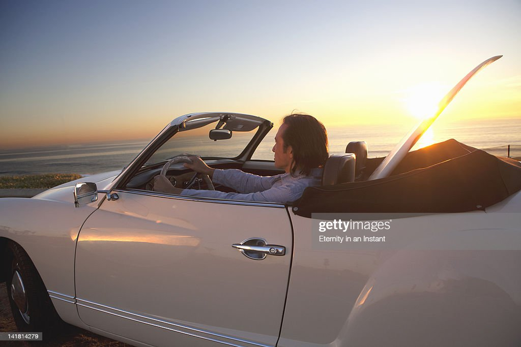 Man with surfboard in car looking at waves