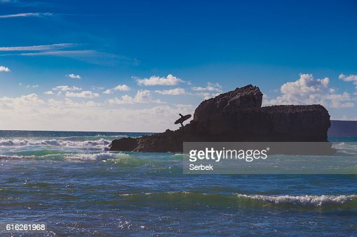 Man with surfboard on large rock at Tonel Beach, Portugal : Stock Photo