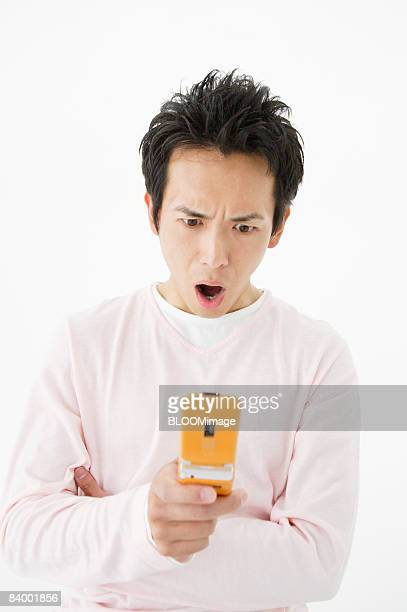 Man with surprised expression, using cellular phone, studio shot