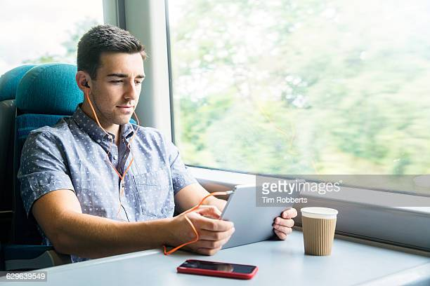 Man with tablet and headphones on train