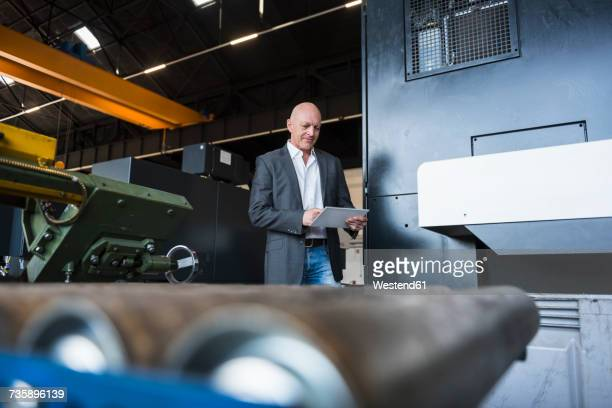 Man with tablet at machine on factory shop floor