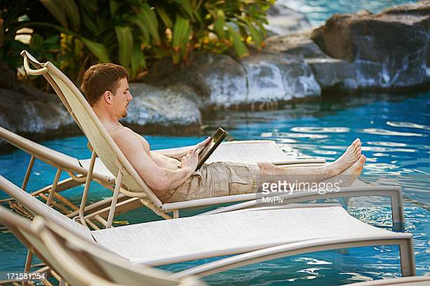 Man with tablet by the pool