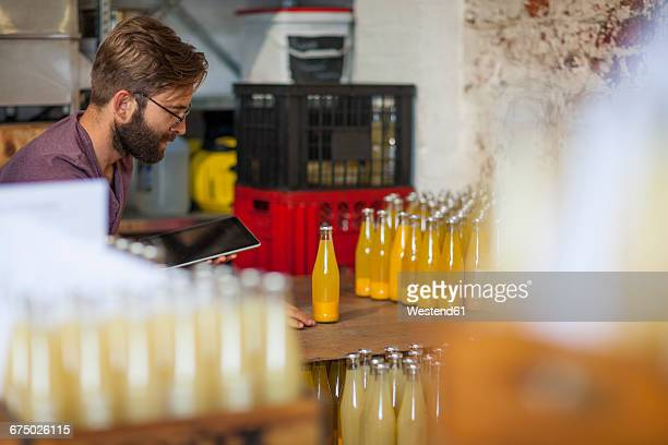 Man with tablet checking stock of juice bottles in warehouse