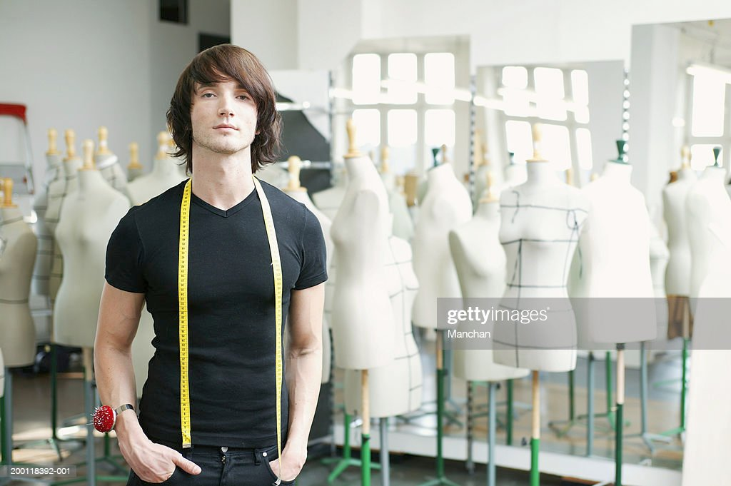 Man with tape measure round neck in fashion studio, portrait : Stock Photo
