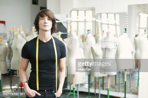 Man with tape measure round neck in fashion studio, portrait